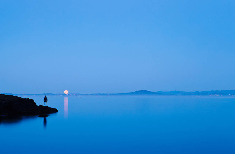 A lone figure standing on a point of land watching the full moon set over the water and Vancouver Island. Haro Strait, San Juan Island, Washington, USA.