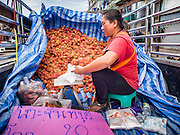 20 JUNE 2014 - SAMUT SAKHON, SAMUT SAKHON, THAILAND: A woman sells lychees to Burmese migrants in Samut Sakhon. Hundreds of thousands of migrant workers from Myanmar work in the Thai fishing industry. Samut Sakhon, (sometimes still called Mahachai, its historical name) is a large fishing port. Many Burmese live in the town and work in the fish process plants. Although hundreds of thousands of Cambodians fled Thailand last week after the military coup, the Burmese workers have stayed and are still working in many Thai towns.    PHOTO BY JACK KURTZ
