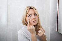 Young woman examining pimples on face in bathroom