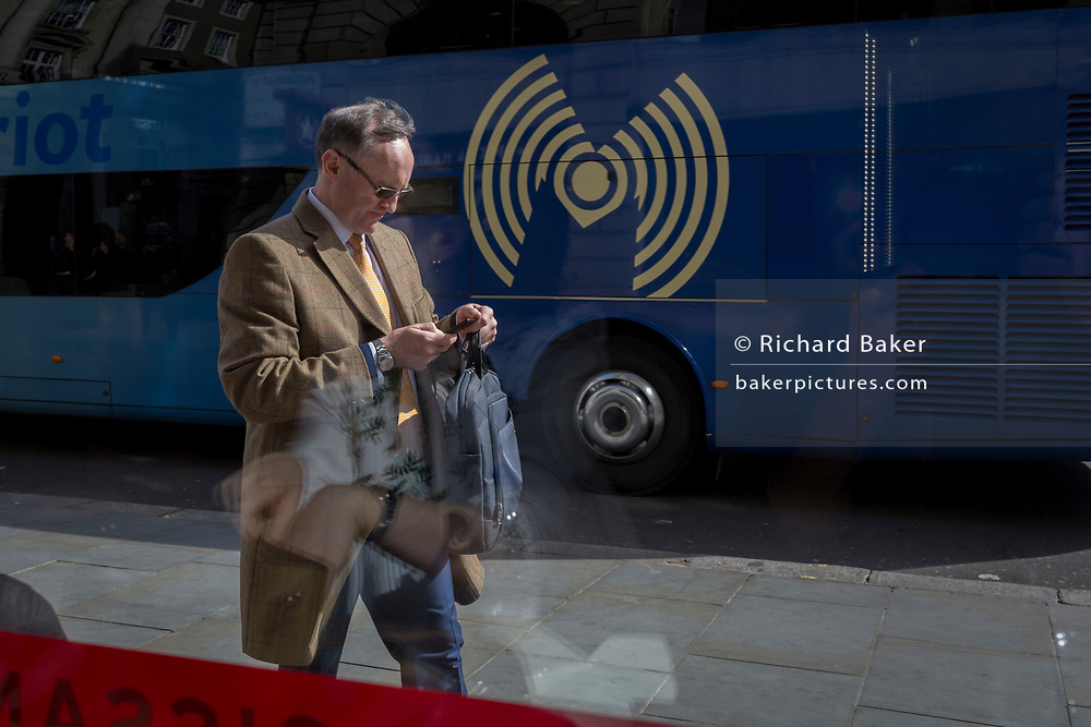 Man checks messages while passing Wifi symbol, on 30th March 2017, in London, England.