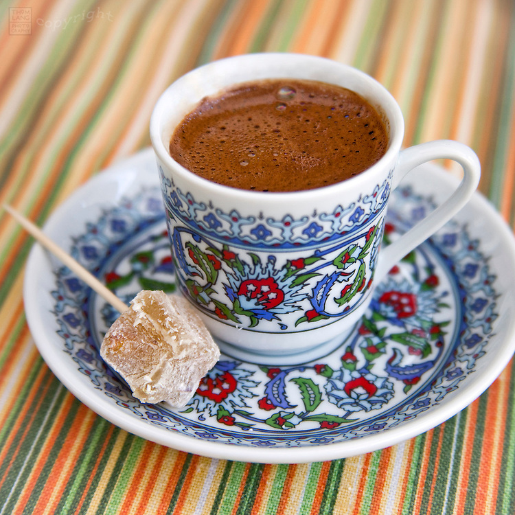 Close-up view of Turkish coffee with a piece of Turkish delight on a toothpick.