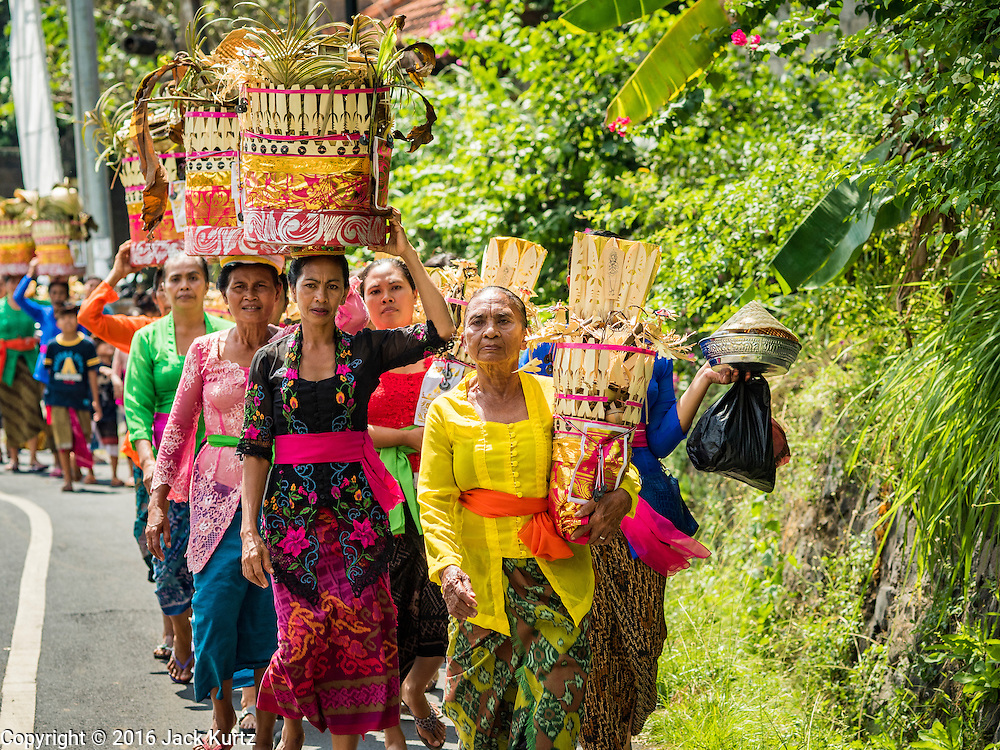 15 JULY 2016 - GIANYAR, UBUD, BALI, INDONESIA: Women carry offerings to be burned with the effigies to the cemetery in Gianyar. Most of the people on Bali are Hindus. Traditional cremations in Bali are very expensive, so communities usually hold one mass cremation approximately every five years. Most of the mass cremations in Bali are held in late June or early July. Gianyar, a small village about 30 minutes from Ubud, held their village wide cremation Friday. The community wide mass cremation in Ubud is Saturday.        PHOTO BY JACK KURTZ
