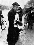 Germany enforced anti-semitism in occupied Poland. On the streets of Warsaw a Jew is selling armbands carrying the Star of David which all Jews were required to wear. 1940-1942.