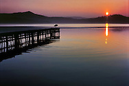 An idyllic sunset scene at Viverone lake in Piedmont, Italy. Ther heron on the jetty was really a nice model, he posed for an entire session while the sun was slowly setting.