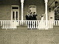 bride is wooed by groomsmen standing on a balcony of an antique brick building in san juan capistrano