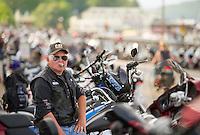 Marty Poulin of Derry enjoys a cigar as he watches motorcyclists parade down Lakeside Avenue Tuesday evening.  (Karen Bobotas/for the Laconia Daily Sun)