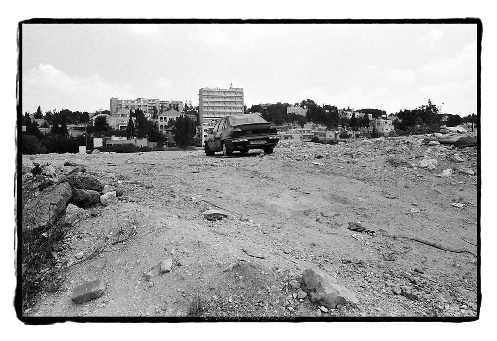 A car stands parked deserted and overlooking the Sheikh Jarrah neighborhood of East Jerusalem. Israel