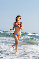 Young woman running through surf on beach front view