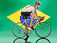 Male Cyclist cycling in front of Brazilian Flag