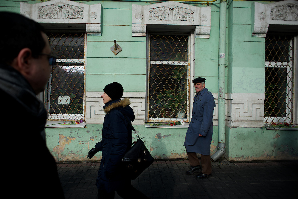 KIEV, UKRAINE - February 24, 2014: People pass by a a building where several anti-government protestors lost their life as when of the attempt to take the Ukraine parliament building in Kiev. CREDIT: Paulo Nunes dos Santos