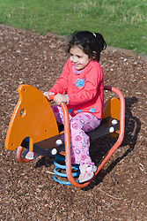 Young girl playing on a playground rocking horse,