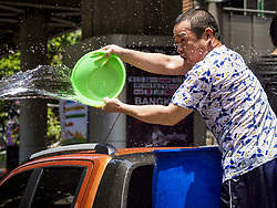 April 13, 2018 - Bangkok, Bangkok, Thailand - A Thai man in the bed of a pickup truck throws a bucket of water on people on Silom Road during the first day of Songkran in Bangkok. Songkran is the traditional Thai New Year celebration best known for water fights. (Credit Image: © Jack Kurtz via ZUMA Wire)