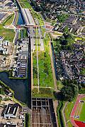 Nederland, Zuid-Holland, Barendrecht, 15-07-2012; Overkapping Barendrecht, constructie gebouwd over 9 spoorlijnen, waaronder HSL en Betuweroute, om geluidsoverlast tegen te gaan. Het station maakt deel uit van de overkapping, verder zijn er op het dak een parkeerterrein en vlinderpark aangelegd. .Links bedrijventerrein Dierenstein, rechts sportpark De Bongerd.The railway station is part of the covering-over of the HST in Barendrecht (SW Netherlands). Roof landscape has a parking lot and a butterfly garden...luchtfoto (toeslag), aerial photo (additional fee required).foto/photo Siebe Swart