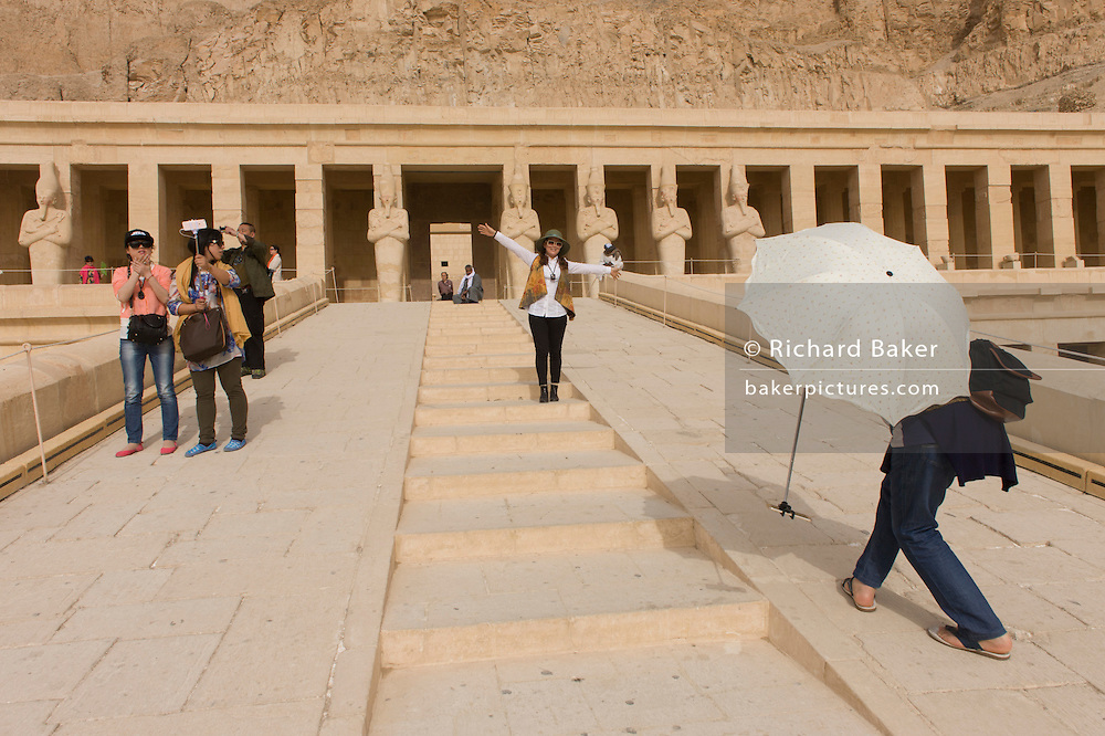 "A Chinese-speaking tourist group enjoy the experience of visiting the ancient Egyptian Temple of Hatshepsut near the Valley of the Kings, Luxor, Nile Valley, Egypt. The Mortuary Temple of Queen Hatshepsut, the Djeser-Djeseru, is located beneath cliffs at Deir el Bahari (""the Northern Monastery""). The mortuary temple is dedicated to the sun god Amon-Ra and is considered one of the ""incomparable monuments of ancient Egypt."" The temple was the site of the massacre of 62 people, mostly tourists, by Islamists on 17 November 1997."