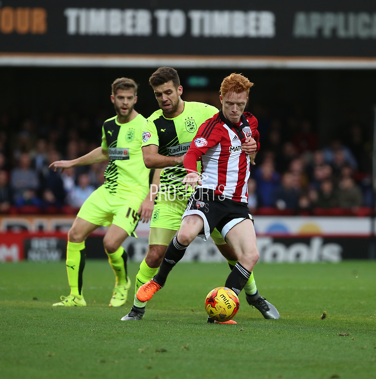 Brentford midfielder Ryan Woods holding off Hudderfield Town defender Tommy Smith during the Sky Bet Championship match between Brentford and Huddersfield Town at Griffin Park, London, England on 19 December 2015. Photo by Matthew Redman.