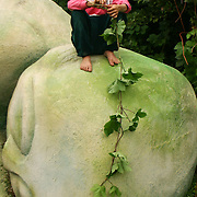 A young Asian girl creates a chain of leaves while sat on a reclining statue at the Free School in East Anglia.