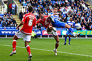 Shane Long (9) of Reading (R) collides with Jason Shackell (4) of Barnsley as Stephen Foster (6) of Barnsley looks on during the Npower Championship match between Reading and Barnsley on Saturday 25th September 2010 at the Madejski Stadium, Reading, UK. (Photo by Andrew Tobin/Focus Images)