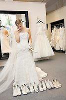 Beautiful young woman confused while selecting footwear in bridal boutique