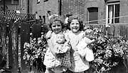 twin sisters holding dolls in backyard 1951