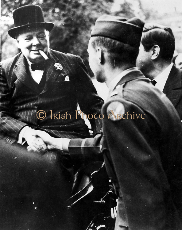 Winston  Leonard Spencer Churchill (1874-1965) British statesman. Churchill, smiling and smoking cigar, shaking hands with a soldier. World War II