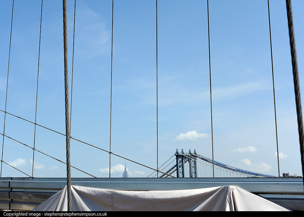 © licensed to London News Pictures. New York, USA  28/05/11.  Manhattan Bridge and the Empire State Building from Brooklyn Bridge.Photo credit should read Stephen Simpson/LNP