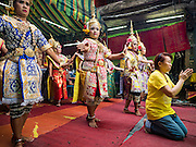 "21 DECEMBER 2015 - BANGKOK, THAILAND: A woman prays while Thai classical dancers perform during the annual rededication of a community Buddhist shrine in Pak Khlong Talat, also called the Flower Market. The market has been a Bangkok landmark for more than 50 years and is the largest wholesale flower market in Bangkok. A recent renovation resulted in many stalls being closed to make room for chain restaurants to attract tourists. Now Bangkok city officials are threatening to evict sidewalk vendors who line the outside of the market. Evicting the sidewalk vendors is a part of a citywide effort to ""clean up"" Bangkok.       PHOTO BY JACK KURTZ"