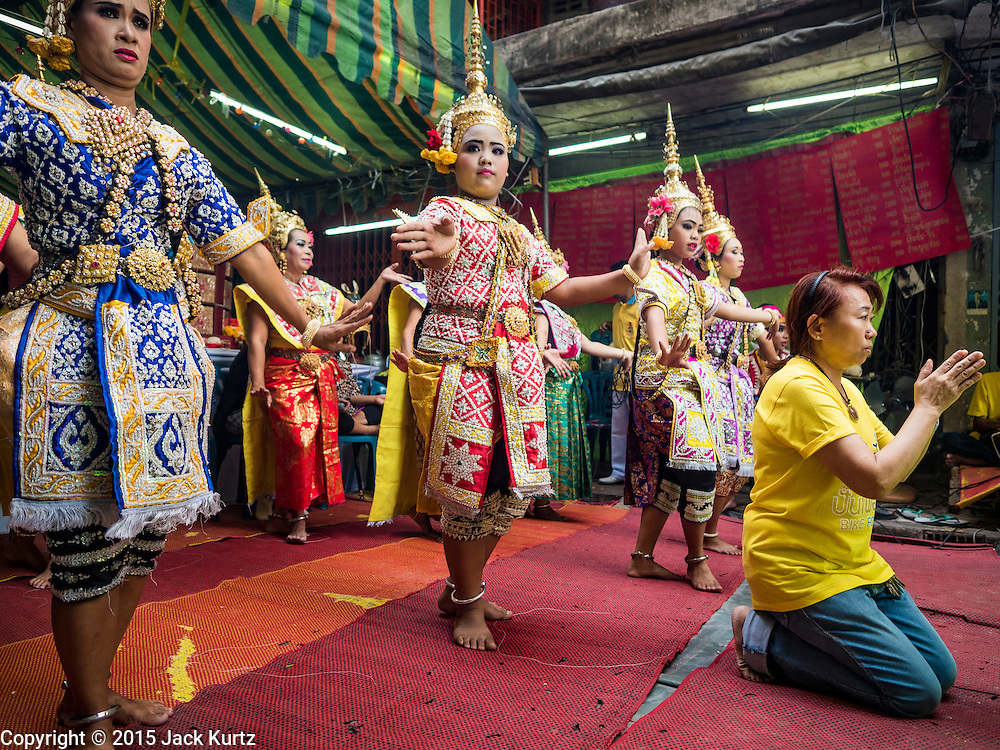 """21 DECEMBER 2015 - BANGKOK, THAILAND: A woman prays while Thai classical dancers perform during the annual rededication of a community Buddhist shrine in Pak Khlong Talat, also called the Flower Market. The market has been a Bangkok landmark for more than 50 years and is the largest wholesale flower market in Bangkok. A recent renovation resulted in many stalls being closed to make room for chain restaurants to attract tourists. Now Bangkok city officials are threatening to evict sidewalk vendors who line the outside of the market. Evicting the sidewalk vendors is a part of a citywide effort to """"clean up"""" Bangkok.       PHOTO BY JACK KURTZ"""