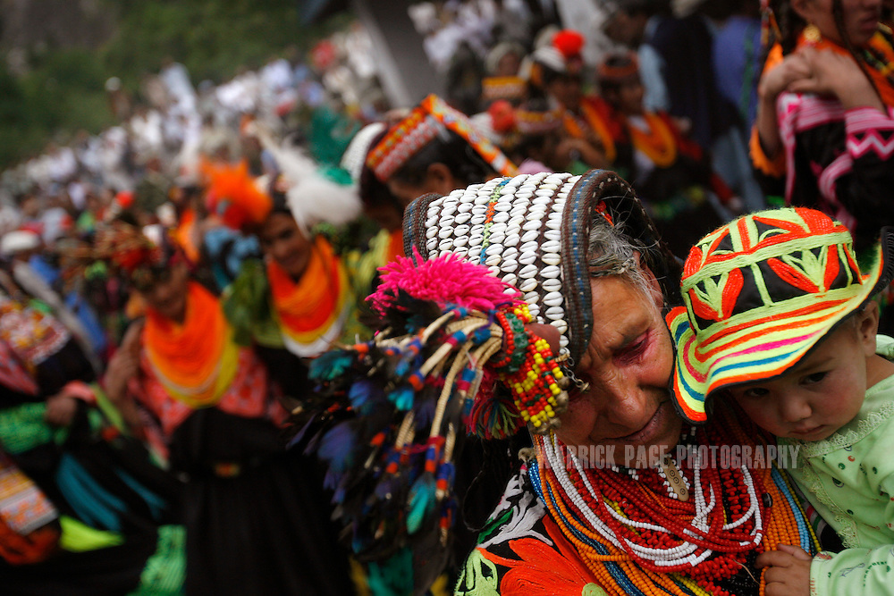 "KALASHA VALLEYS, PAKISTAN - MAY 15: An elderly Kalash woman carries a baby while dancing during the ""Joshi"" (spring) festival in the village of Batrik May 15, 2008 in the Kalasha Valleys, northwestern Pakistan. The Joshi Festival is a celebration of dance, music and prayer to welcome the coming of warmer season and the new life and crops it brings. The shrinking Kalash community of 4000, who claim to be descendants of Alexander the Great and worship several gods, are considered by many Pakistanis to be unclean, lazy and heretics. They often face ridicule and persecution for their polytheistic religion and fear the spread of hard-line Islamism bordering their communities. (Photo by Warrick Page)"