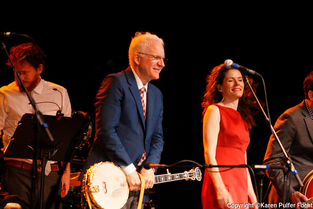 "August 2, 2013 - Comedian Steve Martin, performed at Snowden Grove Amphitheater, Saturday evening, in his more current role as a blue grass musician. He is touring with the North Carolina bluegrass band the Steep Canyon Rangers and singer-musician Edie Brickell (rt)(left). He did use every opportunity to still get a laugh, while performing with his banjo. The Martin-Brickell  pair has collaborated on a musical together. ""Bright Star,"" based on an original story by the two set in the Blue Ridge Mountains in the early 20th century, will have its world premiere September 13 at the Old Globe Theater in San Diego, California."