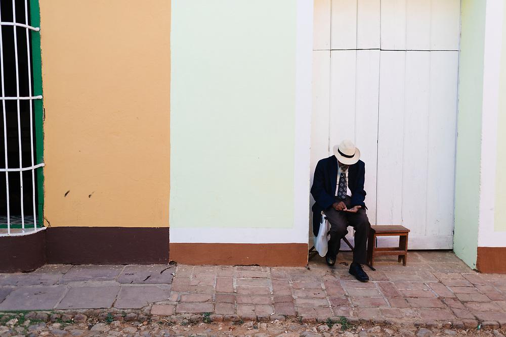 Elderly man counts his money in Trinidad, Cuba