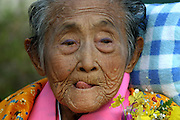Matsu Zakimi (with purple eyeshadow applied by her great-granddaughter) during the celebration for her 97th birthday,at a nursing home near Ogimi Village. Most of the community has turned out to honor the birthdays of three residents. (These are traditional Japanese birthdays, not the actual birth dates. 88, for example is celebrated on the eighth day of the eighth month in the lunar calendar.) Musicians, dancers, and comedians perform as well wishers cheerfully gorge on sushi, fruits, and desserts washed down with beer and saki. (Supporting image from the project Hungry Planet: What the World Eats).