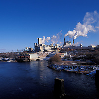 Canada, Ontario, Smoke and steam billow from J. Eddy Pulp and Paper Mill on winter morning in town of Espanola