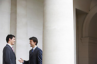 Two business men talking outside building by pillar