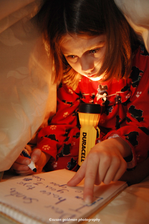 "Madison Rathbun, 7, ducks under the covers in her North Pole, Alaska, home to write a ""Dear Santa"" letter by flashlight, compliments of Duracell. Recently named the ""Official Battery of North Pole,"" the company is supplying batteries and flashlights to all North Pole residents this year. Photo/Duracell, Susan Goldman."