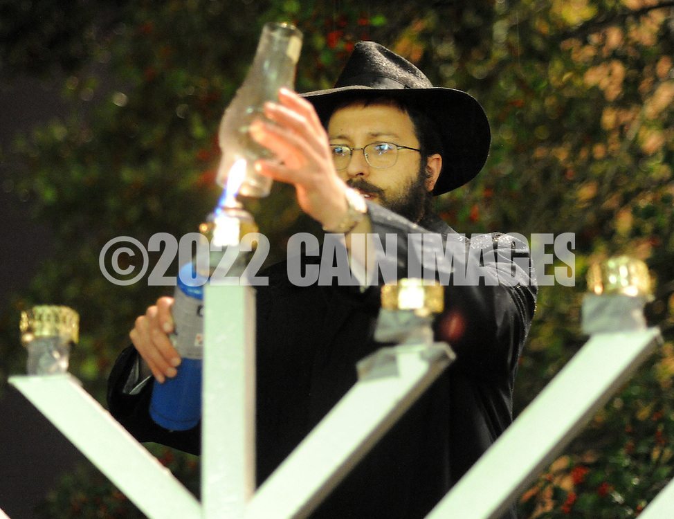 "DOYLESTOWN, PA - DECEMBER 16: Rabbi Mendel Prus of the Lubavitch of Doylestown lights a menorah during a Hanukkah  celebration at the Bucks County Courthouse December 16, 2014 in Doylestown, Pennsylvania. After the lighting of the menorah, the group continued the celebration of the ""festival of lights"" inside the courthouse. (Photo by William Thomas Cain/Cain Images)"