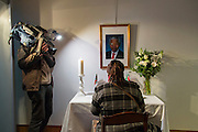 Brussels Belgium 6th December 2013. At the South African Embassy in Brussels people gather. Nelson Mandela died just yesterday.woman signs the book while being filmed by a local tv crew