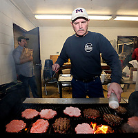 Adam Robison | BUY AT PHOTOS.DJOURNAL.COM<br /> Terry Waldon, of Kossuth, grills up hamburgers for the concession stand Friday night during the Kossuth and East Side game Firday night in Kossuth.
