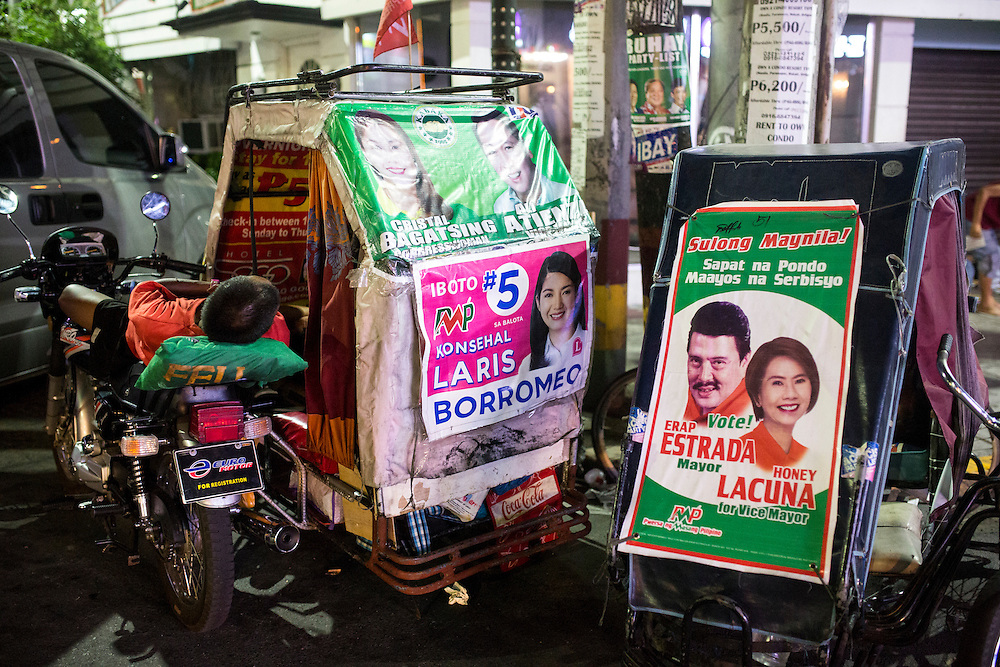 MANILA, PHILIPPINES - MAY 5: A Filipino driver sleeping in his tricycle past midnight in the streets of Manila, Philippines on May 5, 2016.  The 2016 Philippine national elections will be held on 09 May.<br /> <br /> Photo by Richard A. de Guzman