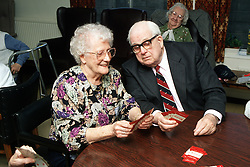 Elderly couple playing game of cards in residential home,