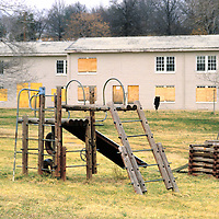 Playground equipment stands amid an abandoned housing project.