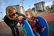 Young girl of three and her mother in a playground on a slide