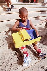 Nursery school boy playing with toy truck sitting on playground steps in Havana; Cuba,
