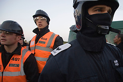 © Licensed to London News Pictures. 19/10/2011. Crays Hill, UK. Police in riot gear wait to enter the site. Residents at Dale Farm, the UK's largest illegal traveller site being evicted today (19/10/2011) following a long dispute with Basildon Council . Travellers and activist had barricaded themselves in to the site in an attempt to prevent their eviction. Photo credit: Ben Cawthra/LNP