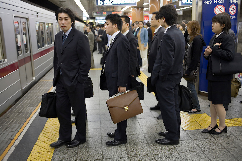 Asia, Tokyo, Japan, Commuters crowd onto subway train platform during morning rush hour