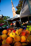People stroll along the organic local produce farmers market in Marion Square in Charleston, South Carolina with St. Mathews Lutheran Church in the background