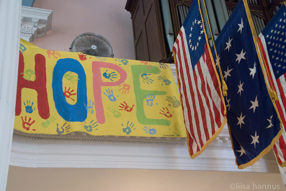 A banner painted with the word Hope and covered in multi-coloured children's hand prints hangs alongside American flags in St. Paul's Chapel in downtown Manhattan, New York City.