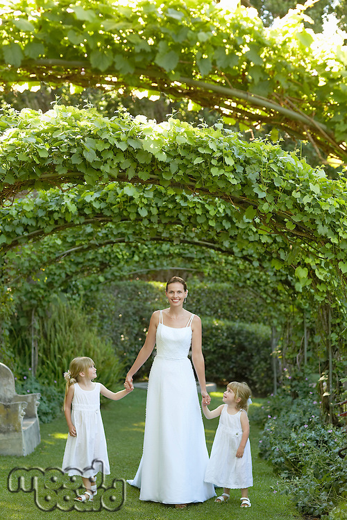 Two young girls and mid adult bride under ivy arches holding hands portrait