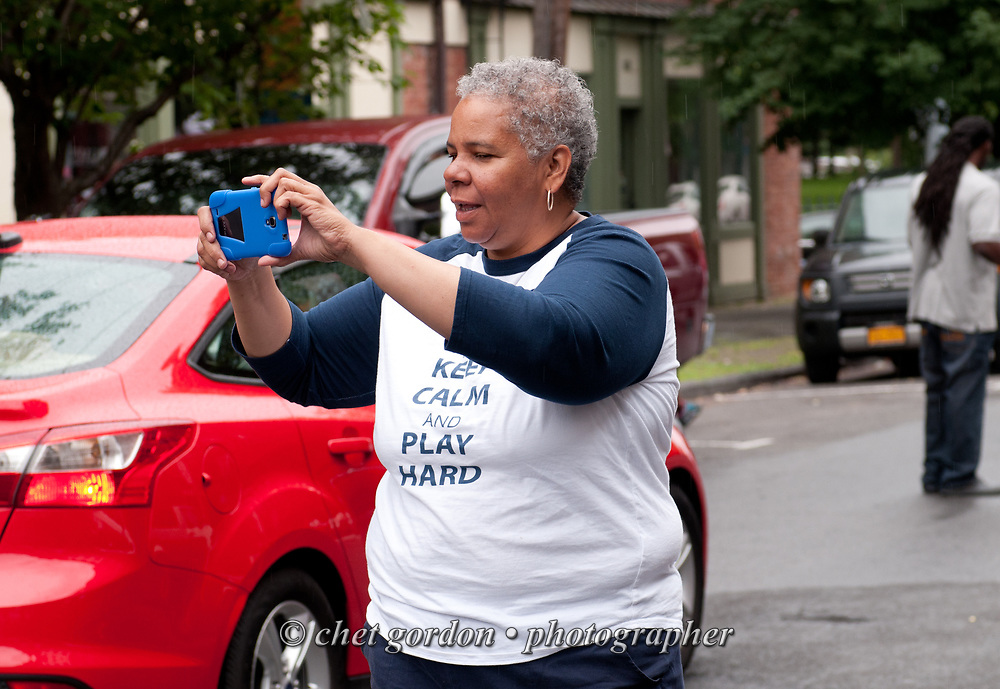 City of Newburgh Councilwoman Gay Lee uses her smartphone to photograph the Newburgh 150th. Anniversary Parade along Liberty Street in Newburgh, NY on Saturday, June 27, 2015. Lee has begun her campaign bid for mayor of Orange County's largest city against incumbent Mayor Judy Kennedy, and Jonathan Jacobson, the former Orange County and Newburgh Democratic Committee Chairman.  © Chet Gordon • Photographer