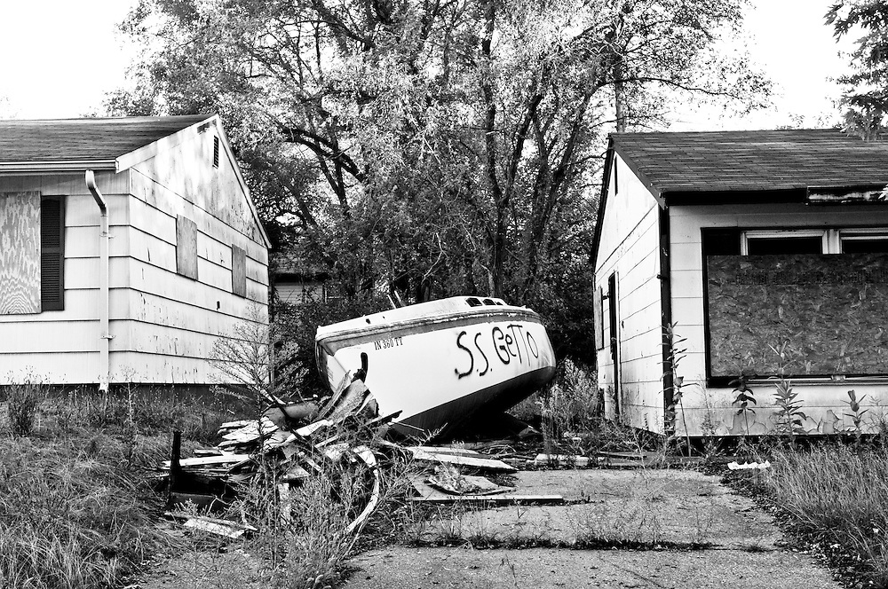 "An abandoned boat spray painted ""S.S. Getto"" rests between two abandoned houses in Gary, Indiana. Gary's population peaked in the early 1960s at roughly 174,000 residents but has fallen to around 80,000 according to the latest U.S. Census in 2010. In addition to the collapsing infrastructure and deteriorating buildings, the number of abandoned houses is sharply increasing as people leave the city. (© William B. Plowman/Redux)"