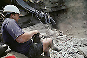 A mining engineer sets off an explosive charge deep inside a mine. The explosives dislodge large pieces of rock from the working face of the mine. When the dust has settled, these rocks are removed and checked for fossil remains. Dinosaur Cove is the world's first mine developed specifically for paleontology, normally the scientists rely on commercial mining to make the excavations. The site is of particular interest as the fossils found date from about 100 million years ago, when Australia was much closer to the South Pole than today. [1989].